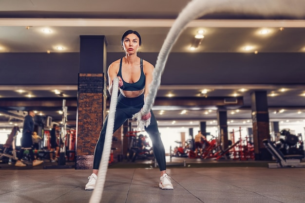 Kaukaski sprawny kobieta ubrana w strój sportowy z linami bojowymi na siłowni