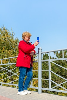 Kaukaski starsza kobieta w czerwonej kurtce za pomocą smartfona w parku