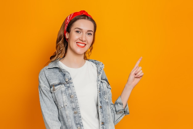 Kaukaski studentka dziewczyna w dżinsowej kurtce, białej koszulce i chustka uśmiecha się i wskazuje palcem na kopię miejsca na białym tle na pomarańczowej ścianie