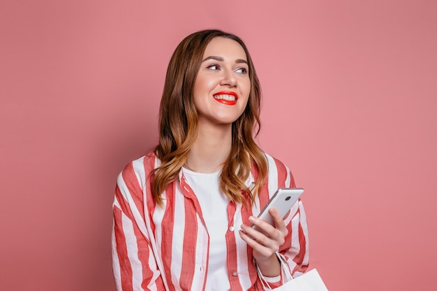 Kaukaski studentka posiada telefon komórkowy i odwraca wzrok. młoda pracownica w czerwonej koszuli w paski trzyma telefon komórkowy w dłoniach i czyta wiadomości na białym tle na różowej ścianie