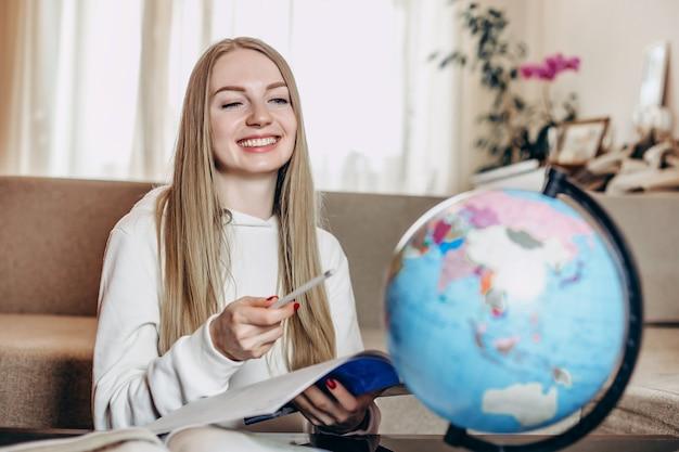 Kaukaski studentka uśmiecha się, trzyma w ręku książkę i studiuje geografię na kuli ziemskiej, siedząc w domu w kwarantannie.