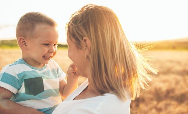 Kaukaski syn i jego blond matka obejmując w polu pszenicy przed słońcem