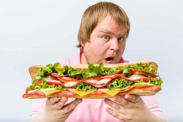 Kaukaski szalony blond grubas trzyma gigantyczną kanapkę