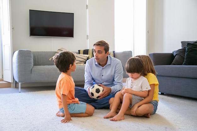 Kaukaski tata trzyma piłkę i rozmawia z dziećmi. kochający ojciec w średnim wieku i dzieci siedzą na podłodze w salonie i bawią się razem. koncepcja dzieciństwa, aktywności w grach i ojcostwa