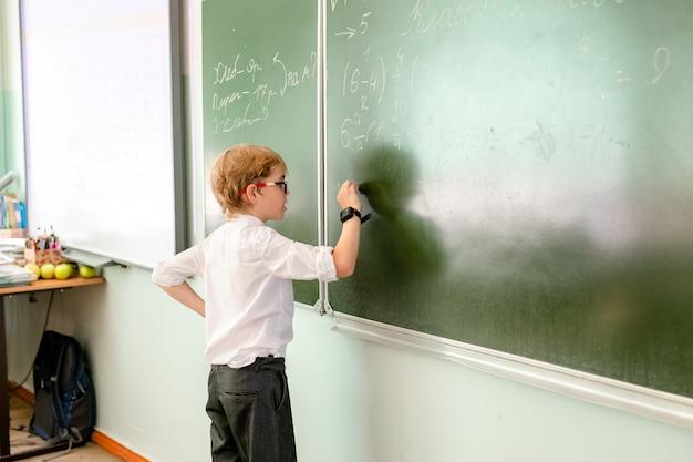 Kaukaski uczeń robi ćwiczeniu przy blackboard w sala lekcyjnej.