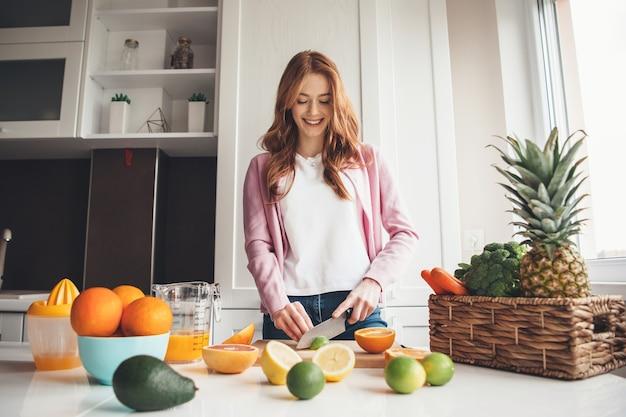 Kaukaski urocza kobieta z piegami i rudymi włosami uśmiecha się podczas krojenia owoców