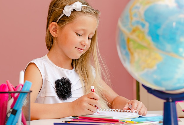 Kaukaski uśmiechnięta dziewczyna jest dong jej pracę domową na lekcji w wieku przedszkolnym