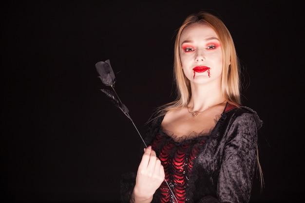 Kaukaski wampir kobieta z zakrwawionymi ustami na czarnym tle. kostium na halloween.