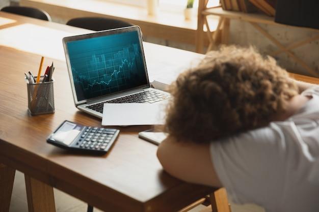 Kaukaski zdenerwowany i zrozpaczony mężczyzna ogląda raporty finansowe i ekonomiczne