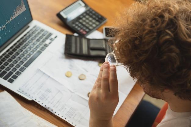 Kaukaski zdenerwowany i zrozpaczony mężczyzna robi raporty finansowe i ekonomiczne, a dochody spadają podczas kwarantanny koronawirusa, problemy. kryzys światowy. obniżenie dochodów, brak pieniędzy, upadek biznesu.