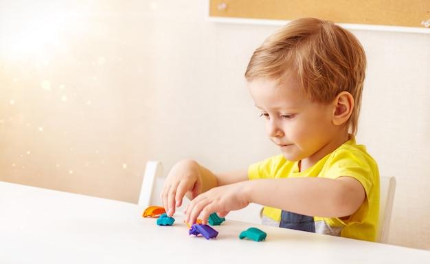 Kaukaskie blond włosy rzeźbi z dziecięcego ciasta do rzeźbienia w domu przy stole, dzieci i kreatywność, rozwój umiejętności motorycznych