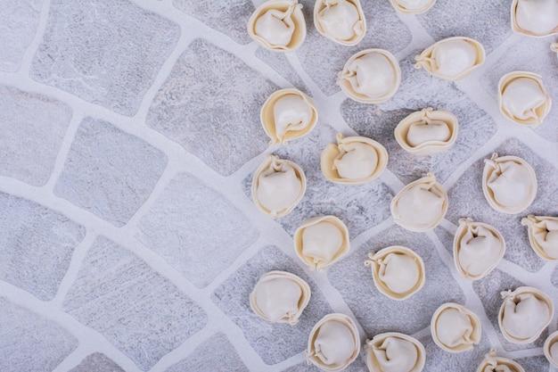 Kaukaskie ciasto chinkali w mące na szarej powierzchni