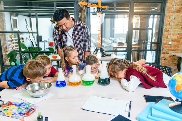 Kaukaskie dzieci w wieku szkolnym w laboratorium chemicznym. uczniowie wkładają suchy lód do kolb z kolorowymi płynami, co powoduje intensywne odparowywanie. nauka, reakcja chemiczna i koncepcja edukacyjna.