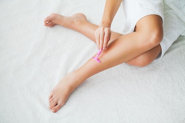 Kaukaskie kobiety golenia nogi z żyletką w domu
