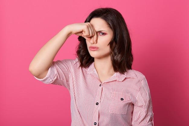 Kaukaskie kobiety ubierają koszulę w paski, czując zapach łóżka, trzymając palce na nosie, cierpiąc z powodu śmierdzącego powietrza, pozując o różową ścianę, stojąc z nieprzyjemnym wyrazem twarzy.