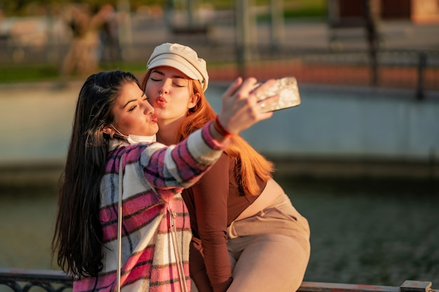 Kaukaskie koleżanki robią selfie w parku