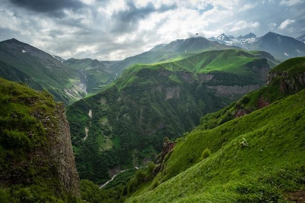 Kaukaskie pasma górskie i doliny w gudauri, georgia. letni dzień na drodze wojskowo-gruzińskiej. gwałtowna zmiana pogody w górach