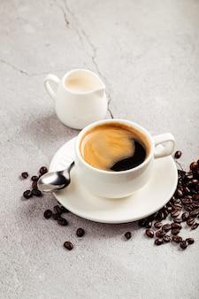Kawa americano w białym kubku z mlekiem w białym dzbanku