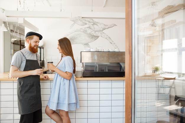 Kawa business concept - młody inteligentny brodaty barman lubią rozmawiać i dając filiżankę kawy do ładnego klienta.