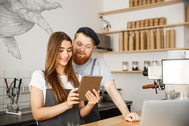 Kawa business concept - zadowoleni i uśmiech właściciele pary spojrzenie na zamówienia tabletów online w nowoczesnej kawiarni