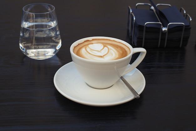 Kawa cappuccino i szklanka wody na stole