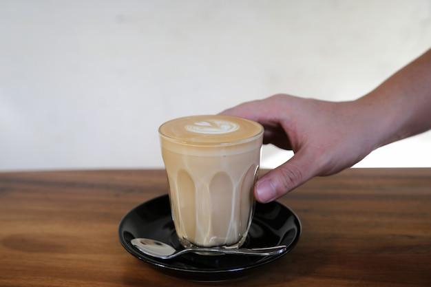 Kawa cappuccino lub latte art z mleka na drewnianym stole w kawiarni