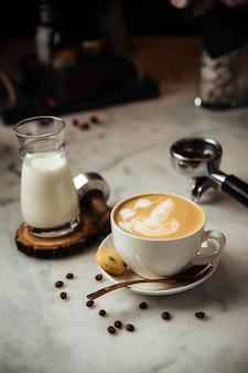 Kawa cappuccino na śniadanie z mlekiem i ciastkami na białym marmurowym stole