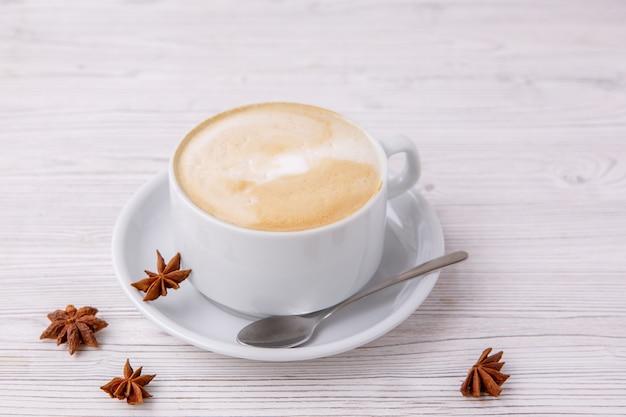 Kawa cappuccino w białej filiżance białe drewniane menu