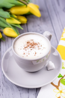 Kawa cappuccino z cynamonem cejlońskim i żółtymi tulipanami