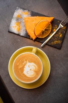 Kawa cappucino w żółtej filiżance z sernikiem w kawiarni