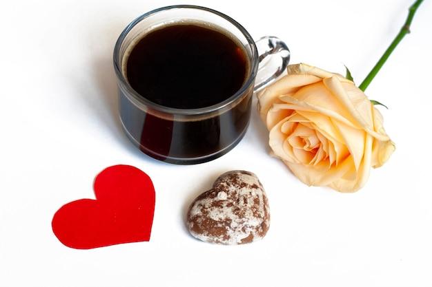 Kawa, ciastka czekoladowe w kształcie serc i żółtej róży na białym tle i czerwone serduszko