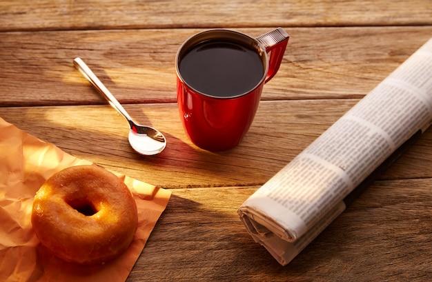 Kawa czerwony kubek gazety i dona rano śniadanie