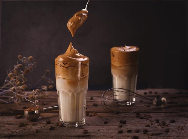 Kawa dalgona. bita lukier z popularną w korei kawą rozpuszczalną kremowy koktajl w wysokich szklankach