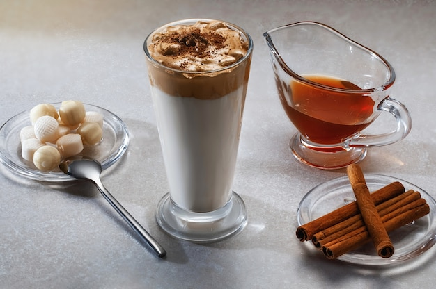 Kawa dalgona - koreański kawowy napój na drewnianym tle. kawa rozpuszczalna lub espresso w proszku ubite z cukrem i gorącą wodą. ja