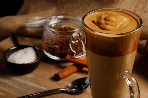 Kawa dalgona - koreański kawowy napój na drewnianym tle. kawa rozpuszczalna lub espresso w proszku ubite z cukrem i gorącą wodą. mrożona bita kawa z dalgony.