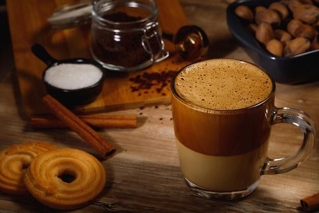 Kawa dalgona - koreański kawowy napój na drewnianym tle. kawa rozpuszczalna lub espresso w proszku ubite z cukrem i gorącą wodą. mrożona koncepcja bitej kawy dalgona. widok z góry.