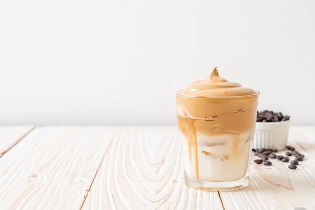 Kawa dalgona. mrożony, puszysty, kremowy, ubity napój typu trend z pianką kawową i mlekiem. modny napój podczas zamknięcia miasta covid-19 i samoobsługowej kwarantanny, koncepcja pozostania w domu.