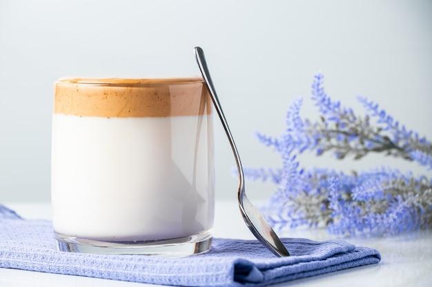 Kawa dalgona. szklanka modnego napoju mlecznego na niebieskiej serwetce.