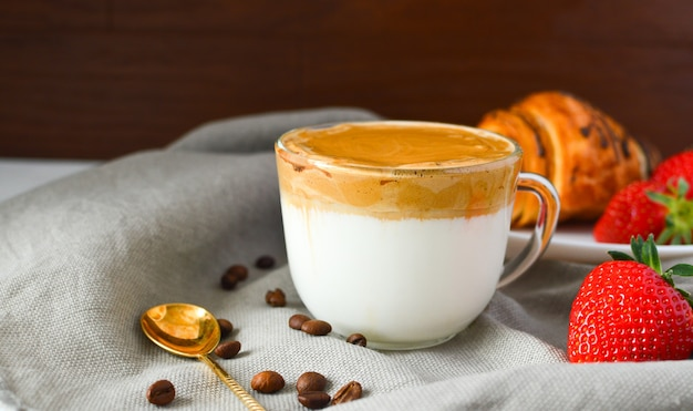 Kawa dalgona w przezroczystej filiżance truskawki, rogalik na ciemnej powierzchni. napój trend. poranna kawa. zdrowe śniadanie.