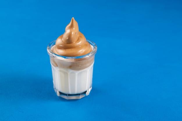 Kawa dalgona w szklance na niebieskim tle. popularny koreański napój z wysoką zawartością pianki kawy rozpuszczalnej.