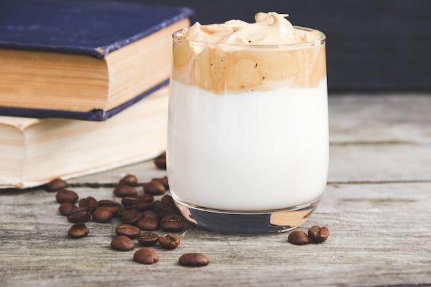 Kawa dalgona ze starymi książkami na drewnianej powierzchni