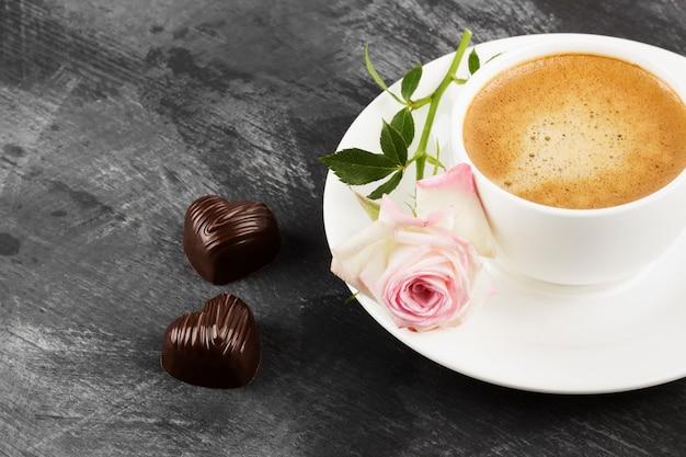 Kawa espresso w białej filiżance, różowej róży i czekoladkach na ciemnym tle