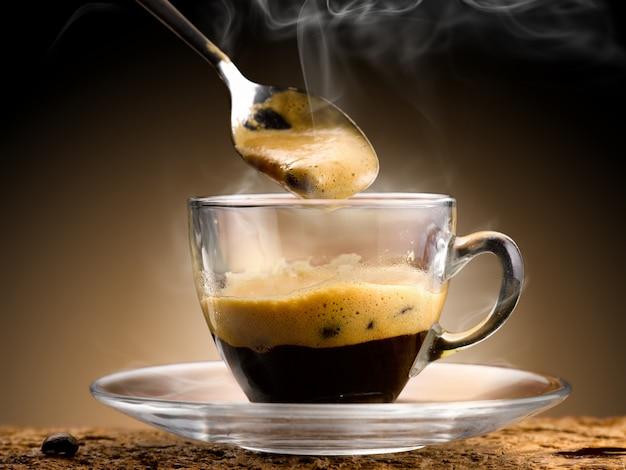 Kawa espresso wlewa się do szklanego kubka