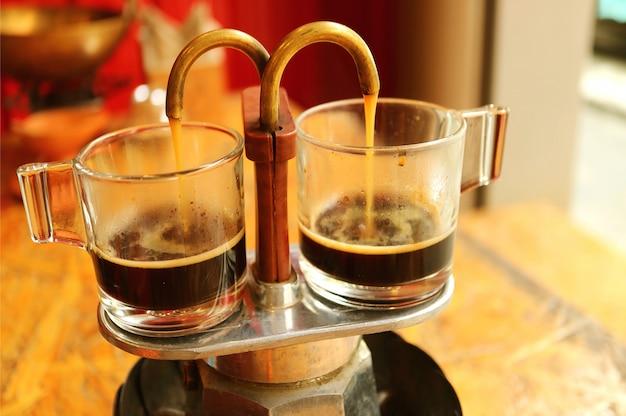 Kawa espresso wypływa z mini dzbanka w stylu retro do szklanki