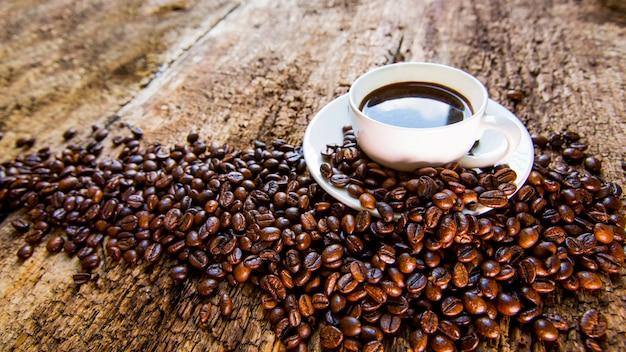 Kawa. filiżanka gorącej kawy i palonych ziaren kawy na drewnianym stole.