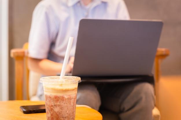 Kawa frappuccino zmieszana ze papierową słomką i kobietą używającą laptopa.