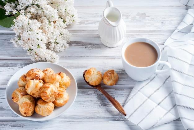 Kawa i eklery na białym stole