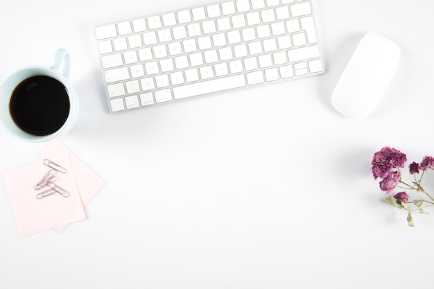 Kawa i kwiaty blisko komputerowej myszy i klawiatury