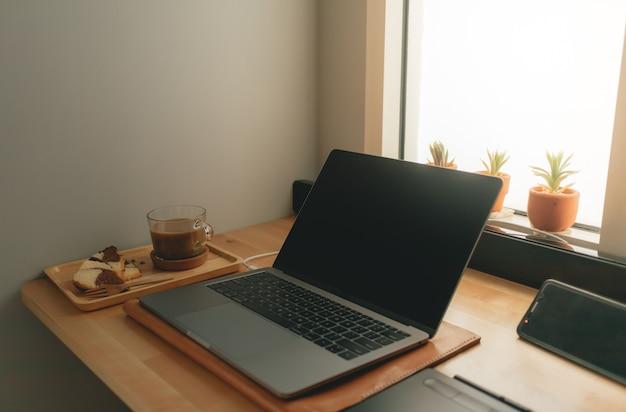 Kawa i laptop na biurku w ciepłym świetle.