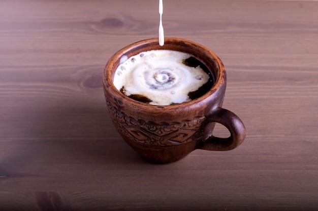 Kawa i mleko w glinianym kubku mleko wlewa się do kawy